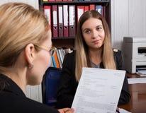 Donna attraente di affari che lavora con i documenti in ufficio donna in un vestito che si siede ad una tavola e ad un segno Fotografie Stock