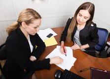 Donna attraente di affari che lavora con i documenti in ufficio donna in un vestito che si siede ad una tavola e ad un segno Fotografia Stock