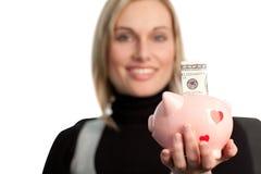 Donna attraente di affari che tiene una banca piggy Fotografie Stock Libere da Diritti