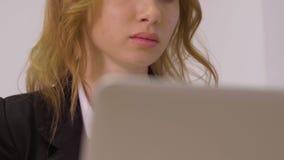 Donna attraente di affari del ritratto che lavora alla fine del computer portatile su video d archivio
