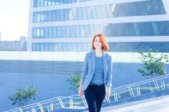 Donna attraente di affari della testarossa sulle scale sui precedenti di un grattacielo Fotografia Stock