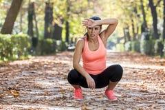 Donna attraente di sport nel boccheggiare respirante degli abiti sportivi del corridore e nella presa della rottura stanca ed esa Fotografia Stock