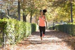 Donna attraente e felice del corridore in abiti sportivi di autunno che esegue a Fotografie Stock Libere da Diritti