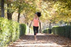 Donna attraente e felice del corridore in abiti sportivi di autunno che esegue a Fotografia Stock