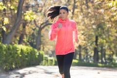 Donna attraente e felice del corridore in abiti sportivi di autunno che esegue a Fotografia Stock Libera da Diritti