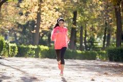 Donna attraente e felice del corridore in abiti sportivi di autunno che esegue a Immagini Stock Libere da Diritti