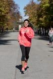 Donna attraente e felice del corridore in abiti sportivi di autunno che esegue a Immagine Stock