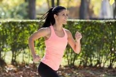 Donna attraente e felice del corridore nel funzionamento e nell'addestramento degli abiti sportivi di autunno sul pareggiare all' Fotografia Stock