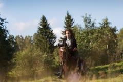 Donna attraente elegante che guida un prato del cavallo Fotografia Stock Libera da Diritti