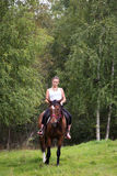 Donna attraente elegante che guida un prato del cavallo Fotografia Stock