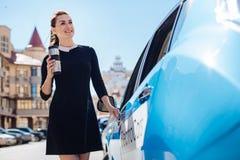 Donna attraente felice che apre la sua automobile fotografia stock