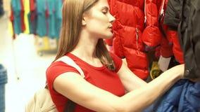 Donna attraente felice nell'acquisto rosso della maglietta in vestiti d'acquisto del centro commerciale Concetto di shopaholism d archivi video