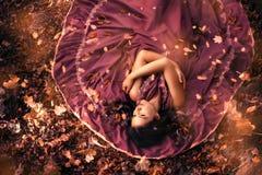 Donna attraente giovane in vestito porpora che si trova in mezzo alle foglie di autunno Vista superiore, caduta delle foglie immagine stock libera da diritti