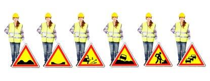 Donna attraente nel casco della costruzione e uniforme con i segnali stradali Fotografia Stock