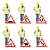 Donna attraente nel casco della costruzione e uniforme con i segnali stradali Fotografie Stock Libere da Diritti