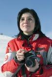 Donna attraente nell'usura di sport che tiene una macchina fotografica Fotografia Stock