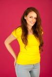 Donna attraente nella posa gialla della maglietta sopra il backgrou rosa vbrant Immagini Stock Libere da Diritti