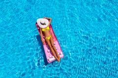 Donna attraente nello stagno con un materasso di galleggiamento fotografia stock libera da diritti