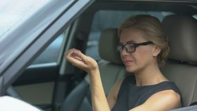 Donna attraente in occhiali che si siedono in automobile, soffrente dal dolore del polso, salute stock footage