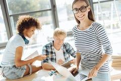 Donna attraente positiva che studia con i suoi groupmates Immagine Stock