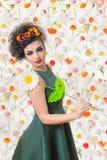 Donna attraente riccia con una grande margherita bianca e un vestito verde Fotografie Stock Libere da Diritti