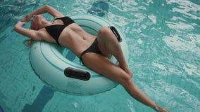 Donna attraente sexy nel nuoto nero del bikini sull'anello di gomma gonfiabile nello stagno 4K video d archivio
