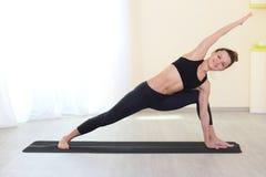 Donna attraente sorridente che fa allenamento di sport in una stanza luminosa Immagine Stock