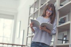 Donna attraente sorridente che legge un libro Fotografie Stock Libere da Diritti