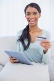 Donna attraente sorridente che per mezzo del suo pc della compressa per comprare online Fotografia Stock Libera da Diritti