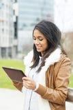 Donna attraente sorridente che utilizza il computer della compressa nello spazio pubblico. Fotografia Stock Libera da Diritti