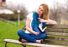 Donna attraente sul banco con il libro Fotografie Stock Libere da Diritti
