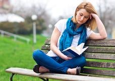 Donna attraente sul banco con il libro Immagine Stock Libera da Diritti