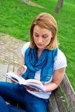 Donna attraente sul banco con il libro Fotografia Stock Libera da Diritti