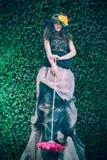 Donna attraente sulla parete naturale delle foglie verdi Fotografia Stock Libera da Diritti