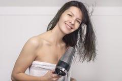 Donna attraente in un asciugamano che asciuga col phon i suoi capelli Fotografie Stock