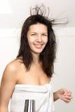 Donna attraente in un asciugamano che asciuga col phon i suoi capelli Immagine Stock