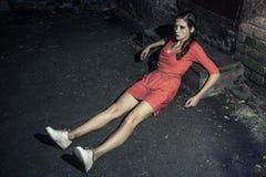 Donna attraente in vestito luminoso che si siede sulla strada e sull'appoggiarsi fotografie stock