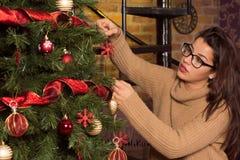Donna attraente in vetri che decora l'albero di Natale Fotografia Stock Libera da Diritti