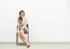 Donna in attrezzatura dell'ufficio che aspetta su una sedia Immagini Stock Libere da Diritti