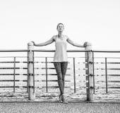 Donna in attrezzatura di forma fisica che si rilassa dopo l'allenamento all'argine Immagini Stock Libere da Diritti