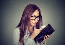 Donna avida che conta eliminando soldi dal suo portafoglio Fotografia Stock Libera da Diritti