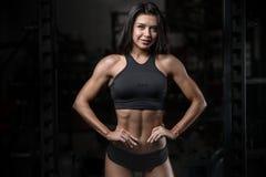 Donna bagnata di forma fisica castana sexy dopo l'allenamento nella palestra Immagine Stock