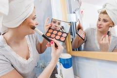 Donna in bagno che applica il bronzer di contorno sulla spazzola Immagine Stock