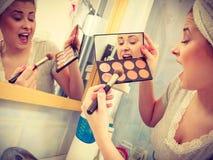Donna in bagno che applica il bronzer di contorno sulla spazzola Fotografia Stock Libera da Diritti