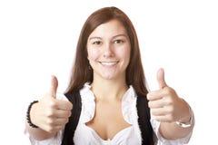 Donna bavarese con il dirndl che mostra i pollici in su. Fotografia Stock