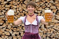 Donna bavarese felice che tiene due boccali con coperchio di birra Immagini Stock Libere da Diritti