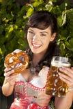 Donna bavarese felice con il dirndl, la birra e la ciambellina salata Immagine Stock