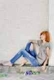 Donna bella che si siede contro la parete che osserva in su Fotografia Stock