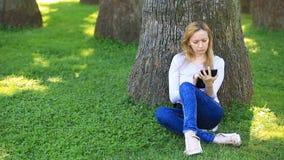 Donna bella che si siede sotto una palma e che passa in rassegna Internet su uno smartphone stock footage