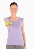 Donna bella che tiene una mela mentre levandosi in piedi Immagini Stock Libere da Diritti